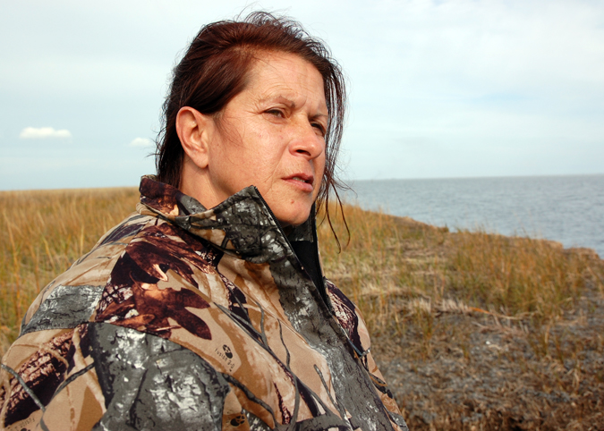 Shrimper Darla Rooks stands on a small island in Louisiana's Bay Jimmy, which has fallen prey to both the BP oil spill and decades of land loss.