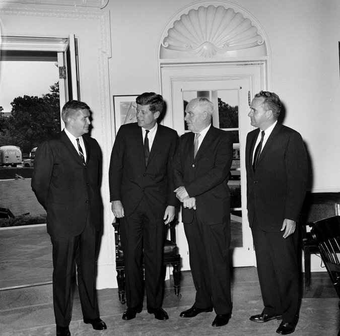 Governor Terry Sanford (left) meets with President John F. Kennedy in the White House Oval Office in 1961. On the other side of Kennedy is Secretary of Commerce Luther H. Hodges; to the far right is an unidentified man. Photo in public domain; courtesy of John F. Kennedy Presidentil Library and Museum.