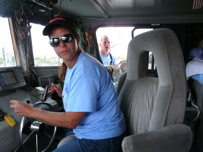 Darla Rooks pilots the Cajun Queen, with her husband and deckhand Todd in the background.